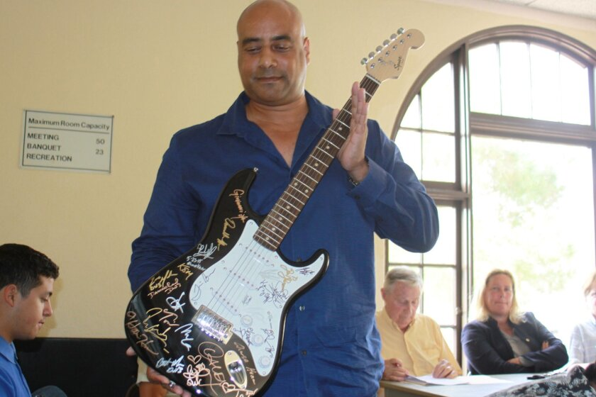 David Payne, organizer of the proposed jazz fest in Scripps Park, shows La Jolla Parks & Beaches board a signed guitar similar to one that would be auctioned off at the festival.