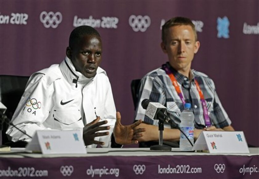 Marathon runner Guor Marial, who is stateless, responds to a question during a news conference at the 2012 Summer Olympics, Friday, Aug. 10, 2012, in London. Marial, from South Sudan, will compete in the marathon under the Olympic flag. Brad Poore, right, helped Marial with his certification to compete in the Olympics. (AP Photo/Darron Cummings)