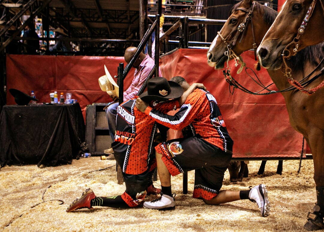 Bull riders kneel and embrace while saying say a quick prayer before entering the MGM Garden Arena.