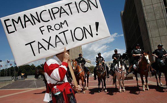 Santa Ana police on horseback watch as protesters leave an anti-tax rally at the Santa Ana Civic Center.