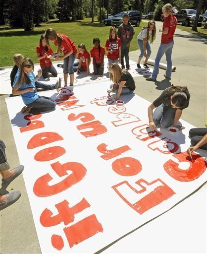 """FILE - In this Sept. 19, 2012 file photo, Kountze High School cheerleaders and other children work on a large banner in Kountze, Texas. A judge on Wednesday, May 9, 2013 ruled that cheerleaders at the high school can display banners emblazoned with Bible verses at football games. The dispute began during the last football season when the district barred cheerleaders from using run-through banners that displayed religious messages, such as """"If God is for us, who can be against us."""" (AP Photo/The"""