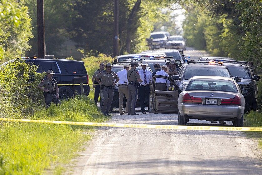 Law enforcement vehicles and personnel gather behind yellow tape