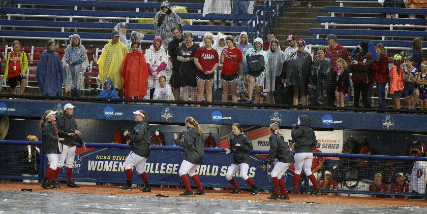 The Alabama team passes time while fans watch during a rain delay in the Women's College World Series NCAA softball game between Oklahoma and Alabam in Oklahoma City, Thursday, June 2, 2016. (Bryan Terry/The Oklahoman via AP)
