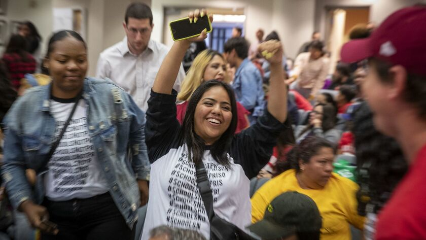 Audience members celebrate after the LAUSD school board voted June 18 to end their controversial policy of interrupting classes to randomly search students with metal detector wands,
