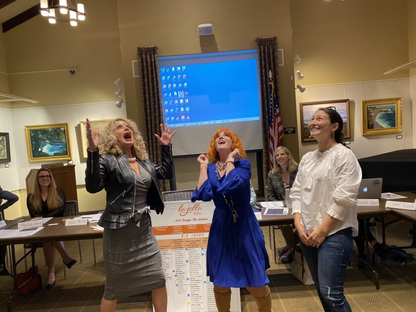 A coin tossed by La Jolla Village Merchants Association executive director Jodi Rudick, center, breaks the tie vote to determine the organization's next treasurer between Kelli Metcalf and Lauren Johnston at the Nov. 13 meeting in the La Jolla Library.
