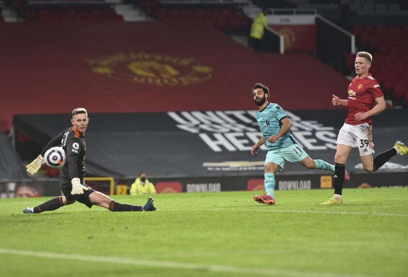 El egipcio Mohamed Salah anota el cuarto gol de Liverpool ante Manchester United en el encuentro de la Liga Premier disputado el jueves 13 de mayo de 2021 (Peter Powell/Pool via AP)