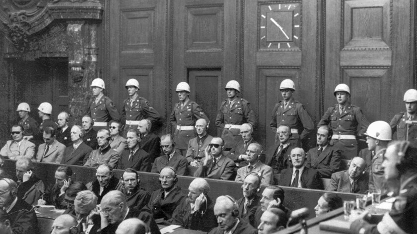 War crimes trial defendants (seated in the back two rows, directly in front of the helmeted military police) listen to partial verdicts inside the Palace of Justice in Nuremberg, Germany on Sept. 30, 1946. Many were executed weeks later.