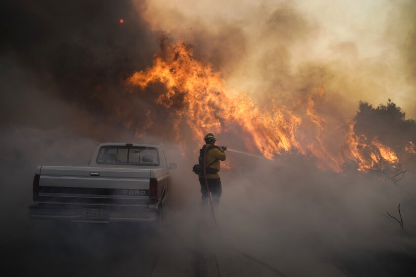 A firefighter next to a Ford truck battles a raging fire amid smoke