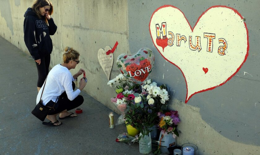 Lynn Ross, left, watches Cathy Riley apply a heart-shaped card to a wall on San Diego Place at the south end of Misson Blvd. where Maruta Gardner lost her life Friday after being hit by an alleged DUI driver.  Both women work for Bird Rock Dental where Gardner was a patient.
