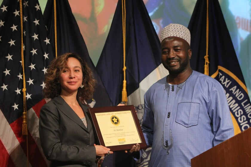TLC Commissioner Meera Joshi, presents a certificate of achievement to Ali Abubakar, who was one of the hundreds of New York City taxi drivers honored on Wednesday for their safety record.
