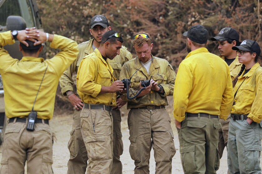 Firefighters huddle to plan their attack on the Bobcat fire in the San Gabriel Mountains on Tuesday.