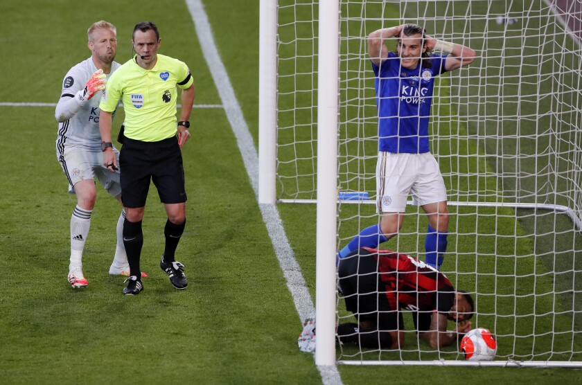Leicester City goalkeeper Kasper Schmeichel, left, appeals to referee Stuart Attwell after Bournemouth's Dominic Solanke, not pictured, scores his side's second goal of the game and Leicester City's Caglar Soyuncu, right, is sent off following a challenge on Bournemouth's Callum Wilson during the English Premier League soccer match between Bournemouth and Leicester City at Vitality Stadium in Bournemouth, England, Sunday, July 12, 2020. (AP Photo/Andy Couldridge,Pool)
