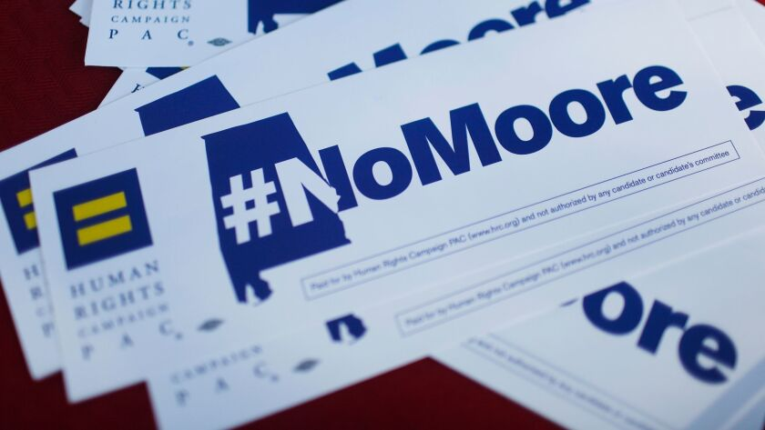 """Bumper stickers saying """"#NoMoore"""" sit on a table during a protest of Republican Senate candidate Roy Moore in Montgomery, Ala., on Nov. 28."""