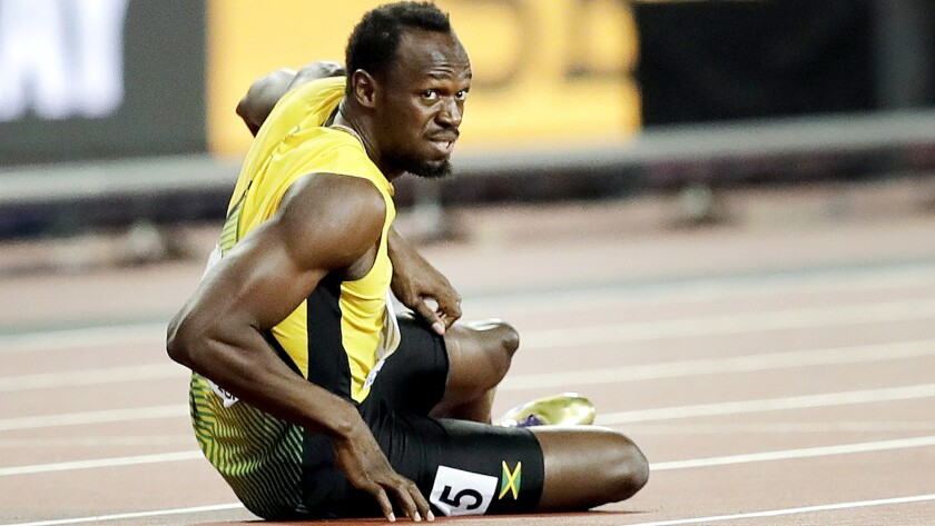 Jamaica's Usain Bolt lies on the track after he injured himself during the 4x100 m relay final durin