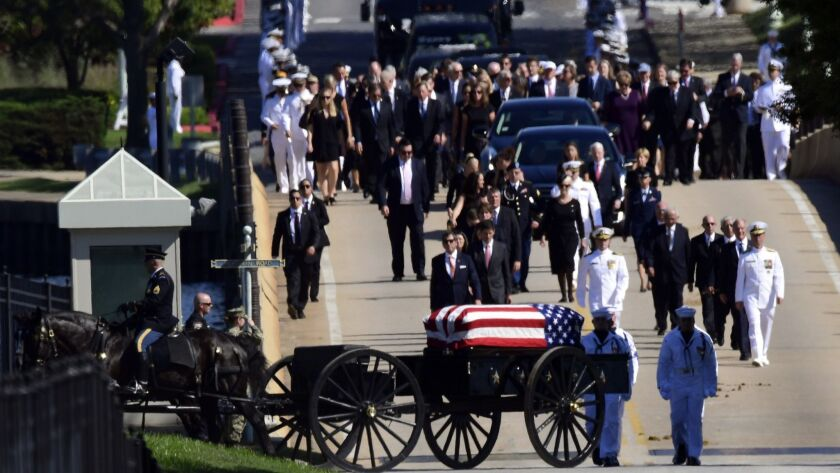 Family members follow a horse-drawn caisson carrying the casket of Sen. John McCain to the Naval Academy cemetery in Annapolis, Md., on Sunday.