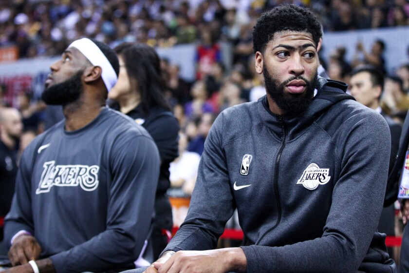 Lakers stars LeBron James, left, and Anthony Davis sit on the bench during an exhibition game against the Brooklyn Nets on Oct. 12.