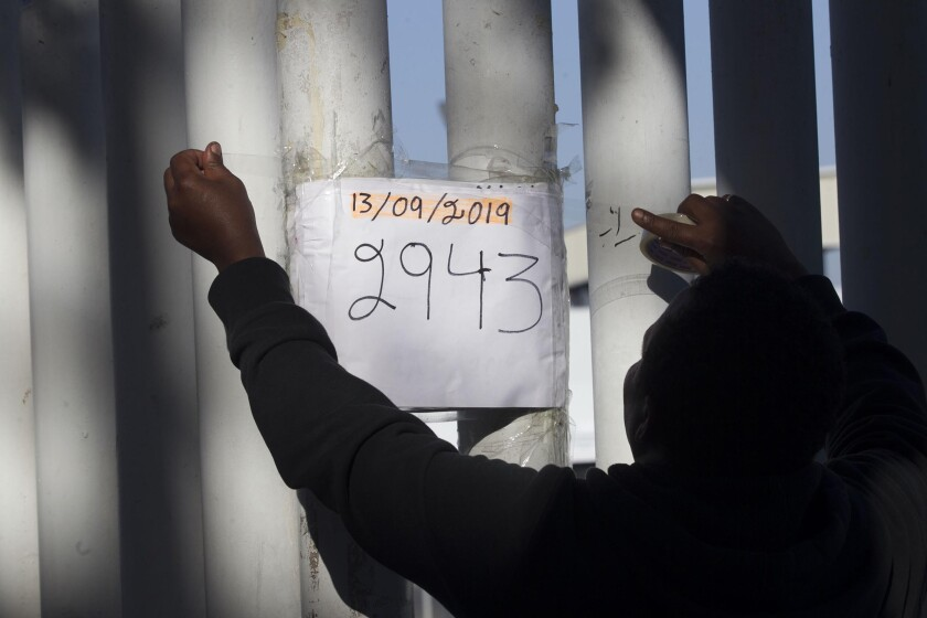 A migrant volunteer posts the newest number sign indicating where they are in the wait list of numbers that have been given out to asylum seekers so they could be taken to the U.S. for processing on Friday, September 13, 2019 in Tijuana, Baja California, Mexico. Each number represents 10 names on the list.