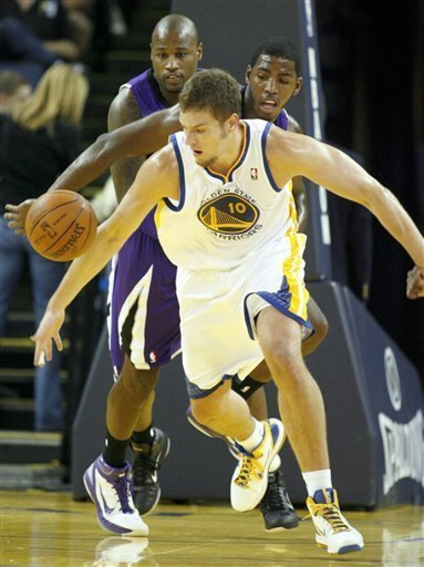 The Golden State Warriors' David Lee (10) eyes a loose ball in front of the Sacramento Kings' Darnell Jackson, back left, and Jason Thompson in the first half of an NBA preseason basketball game, Sunday, Oct. 10, 2010 in Oakland, Calif. (AP Photo/Dino Vournas)