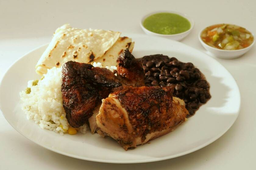 Chicken from Pollo a la Brasa is wood-roasted. You can get rice and beans on the side.