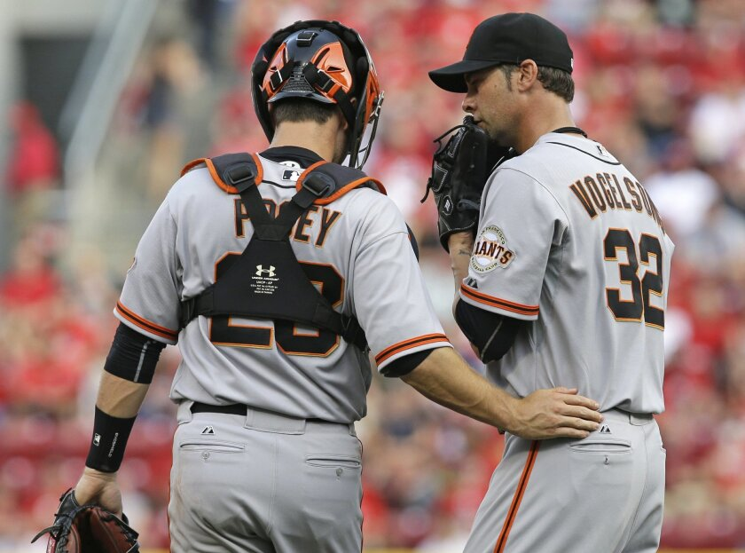 San Francisco Giants catcher Buster Posey (28) talks with starting pitcher Ryan Vogelsong (32) in the first inning of a baseball game against the Cincinnati Reds, Wednesday, June 4, 2014, in Cincinnati. (AP Photo/Al Behrman)