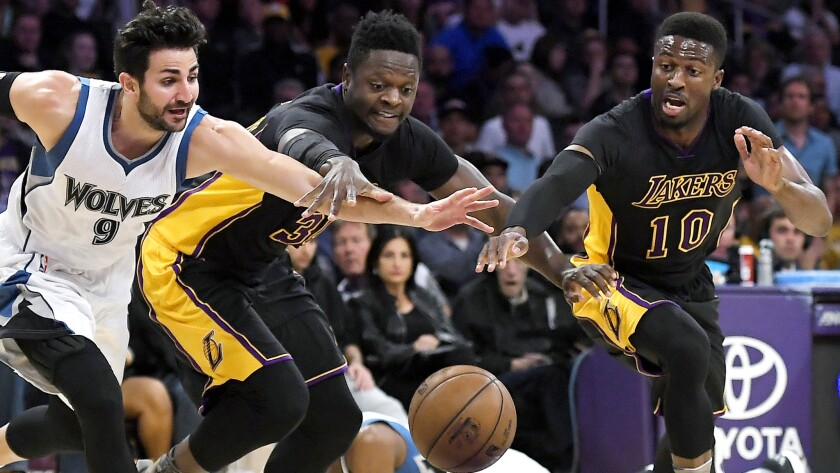 Lakers forward Julius Randle, center, and guard David Nwaba, right, chase after a loose alongside Timberwolves guard Ricky Rubio during the first half Friday. (Mark J. Terrill / Associated Press)