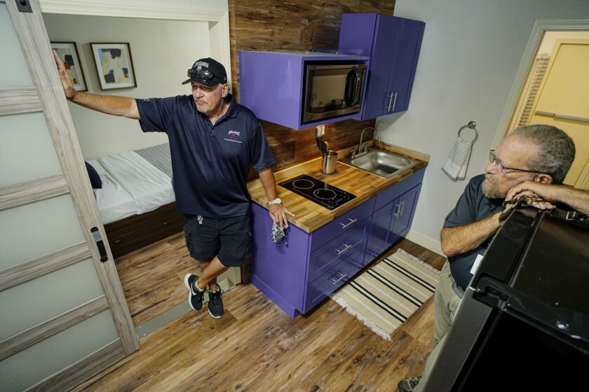 Alpha Project President/CEO Bob McElroy, left, and Strategic Operations owner Stu Segall show a converted shipping container.