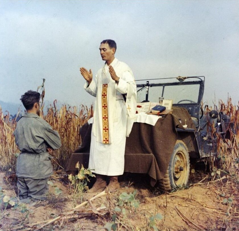 Father Emil Kapaun celebrates Mass using the hood of his jeep as an altar as his assistant Patrick J. Schuler, kneels in prayer in Korea on Oct. 7, 1950.