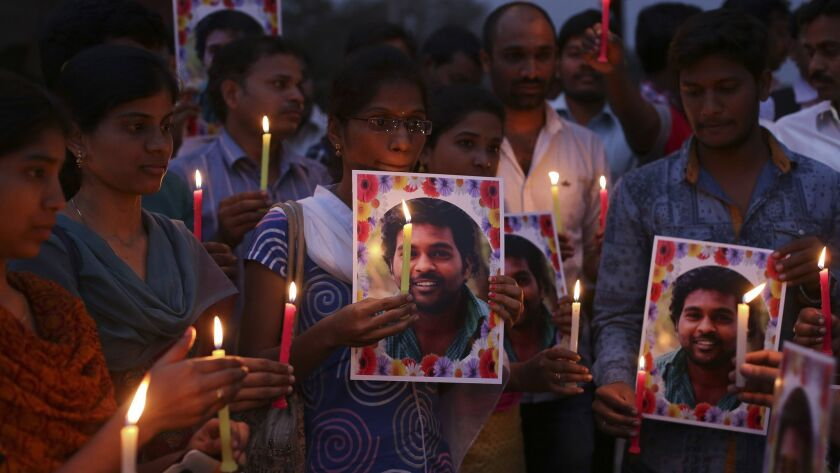 Activists of a Dalit organization participate in a candlelight vigil holding photographs of Indian student Rohith Vemula in Hyderabad, India, Wednesday, Jan 20, 2016.