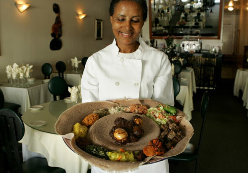 Genet Agonafer, chef and owner of Meals by Genet, holds a plate of traditional Ethiopian food offered at her restaurant in Little Ethiopia.