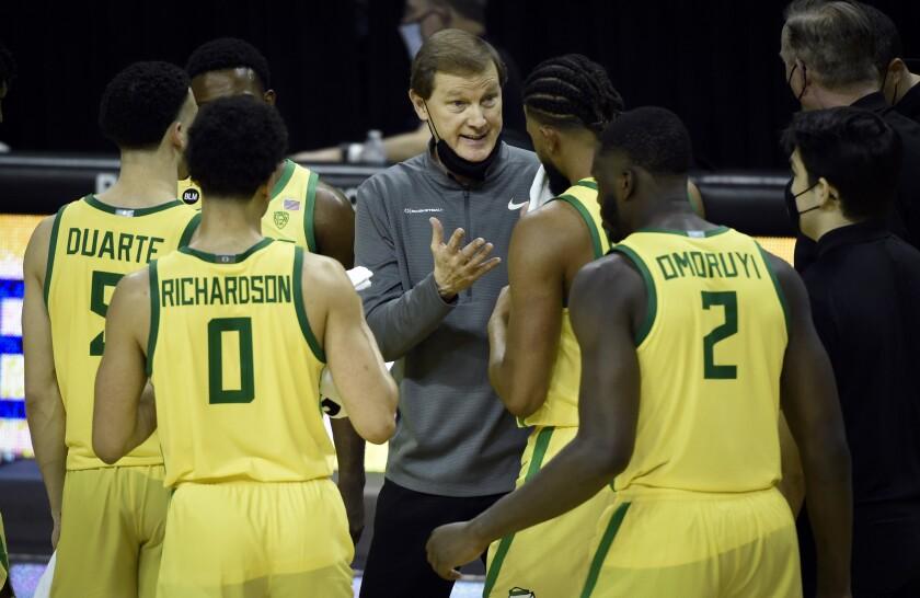Oregon coach Dana Altman talks with his team.