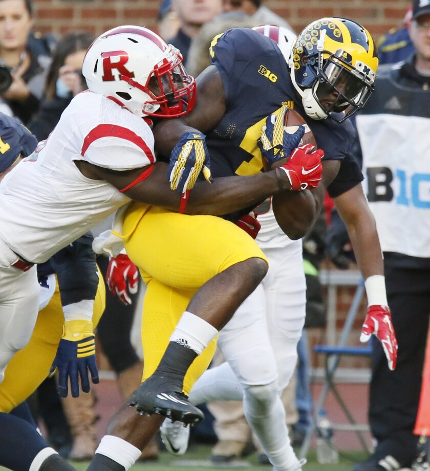 Michigan's De'Veon Smith (4) is tackled by Rutgers' Steve Longa during the first half of an NCAA college football game Saturday, Nov. 7, 2015, in Ann Arbor, Mich. (AP Photo/Duane Burleson)