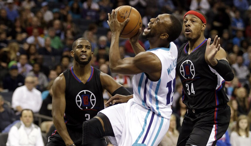 The Charlotte Hornets' Kemba Walker tries to get his shot off as he looks for a foul to be called against the Clippers' Chris Paul (3) or Paul Pierce during the first half on Wednesday.