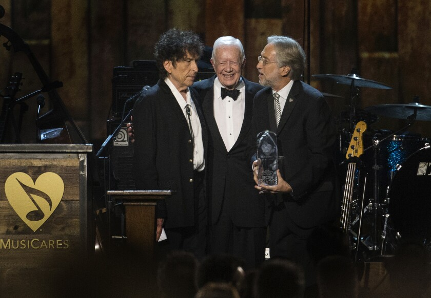 Former President Jimmy Carter introduces Bob Dylan as the 2015 MusiCares Person of the Year with Neil Portnow, president of the National Academy of Recording Arts and Sciences, during the MusiCares concert at the Convention Center.