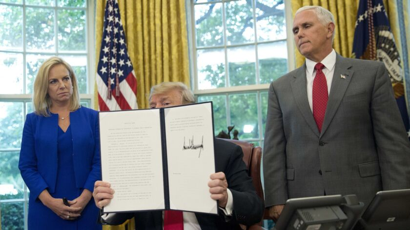 President Donald Trump holds up an executive order he signed to end family separations at the border.