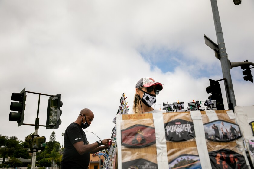 Andre Smith and Angelique Newton sell face masks at the corner of College Avenue and University Avenue.