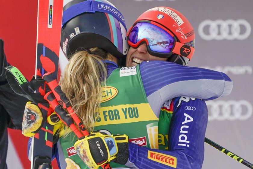 Italy's Marta Bassino hugs, left, teammate Federica Brignone sin the finish area of an alpine ski, women's World Cup giant slalom in Soelden, Austria, Saturday, Oct. 17, 2020. Bassino won the race as Brignone finished in second place. (AP Photo/Giovanni Auletta)