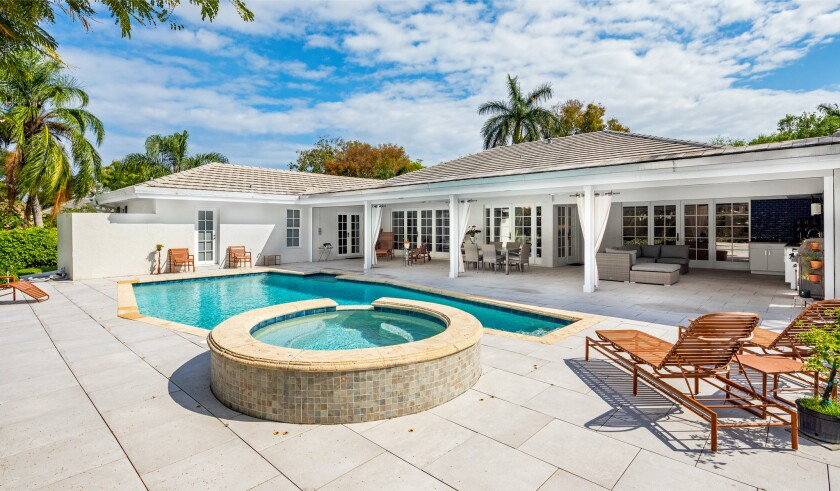 The half-acre property holds a 3,922-square-foot home with a saltwater pool and spa out back.