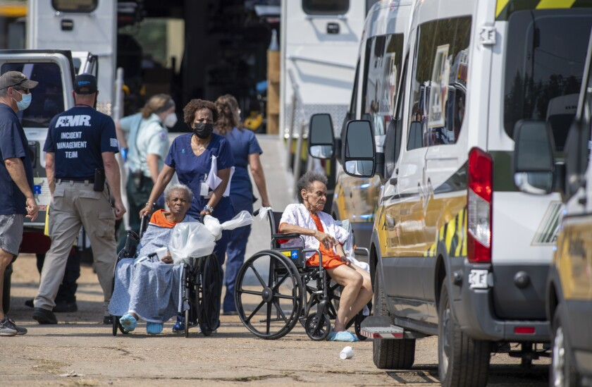 FILE - Paramedics evacuate people at a mass shelter Thursday, Sept 2, 2021, in Independence, La. The owner of nursing homes evacuated to a warehouse says Louisiana health officials approved the plan and inspectors OK'd preparations just before Hurricane Ida hit. Days after the storm, the health department found the warehouse filthy and unsafe. (Chris Granger/The Times-Picayune/The New Orleans Advocate via AP, File)