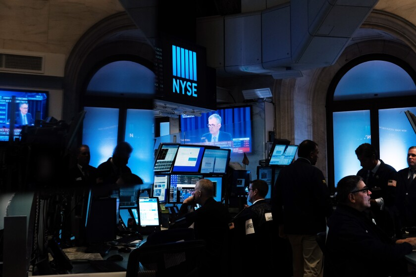 Federal Reserve Chairman Jerome H. Powell shown on a TV screen as traders work on the floor of the New York Stock Exchange.