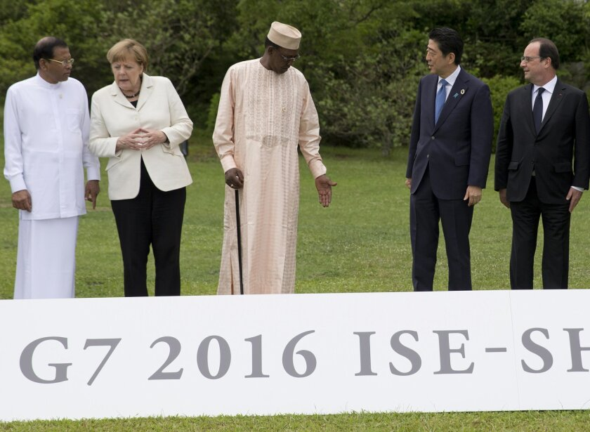 Leaders from left, Sri Lankan President Maithripala Sirisena, German Chancellor Angela Merkel, Chad President Idriss Deby Itno,  Japanese Prime Minister Shinzo Abe and French President Francois Hollande, leave a space for U.S. President Barack Obama, as they wait for him to arrive for a photo sessi
