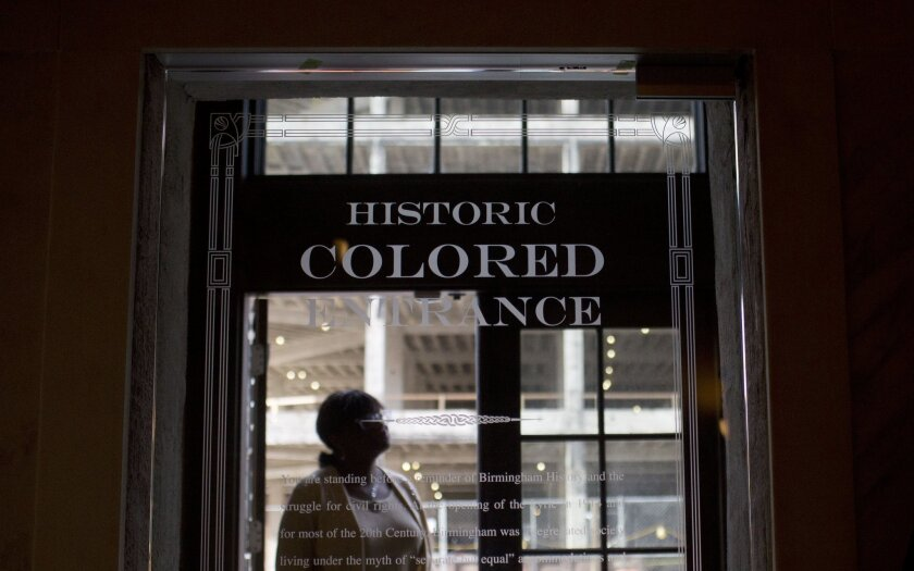 A woman stands in the doorway of the new Historic Colored Entrance at the Lyric Theatre, in Birmingham, Ala. on Jan. 7.