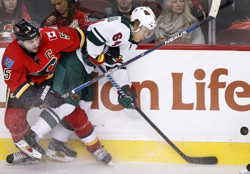 Minnesota Wild's Mikael Granlund, right, from Finland, competes for the puck with Calgary Flames' Mark Giordano during the second period of an NHL hockey game Wednesday, Feb. 17, 2016, in Calgary, Alberta. (Larry MacDougal/The Canadian Press via AP)