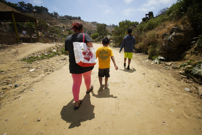 Antonia Portillo, 44, and her two children, Jon and Christian, walk back to the Embajadores shelter where they have been staying in Tijuana on Thursday. Portillo always keeps her children with her because she believes they will be kidnapped. She has submitted her paperwork asking for asylum in the U.S. and is currently waiting in Tijuana for her federal court date scheduled in July.
