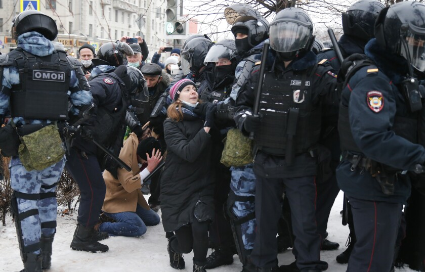 Police detain a man, on his knees amid snow, as another officer stops a young woman.