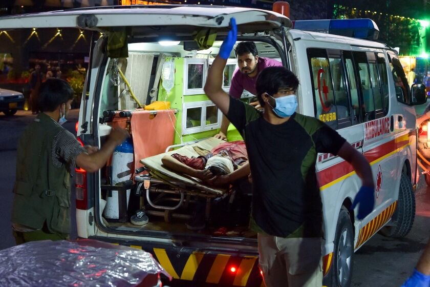 A person with a bandaged head lies on a stretcher in an ambulance with three medical workers nearby
