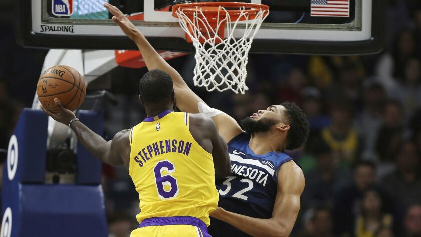 Los Angeles Lakers' Lance Stephenson tries to make a basket over Minnesota Timberwolves' Karl-Anthon