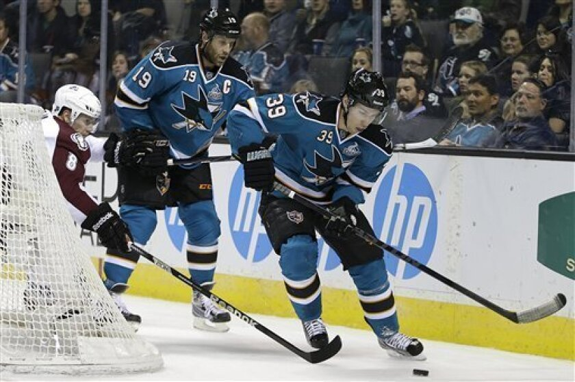 CORRECTS MONTH TO FEBRUARY, NOT MARCH - San Jose Sharks' Logan Couture (39) advances the puck with Joe Thornton (19) past Colorado Avalanche's Jan Hejda (8) during the first period of an NHL hockey game, Tuesday, Feb. 26, 2013, in San Jose, Calif. (AP Photo/Ben Margot)