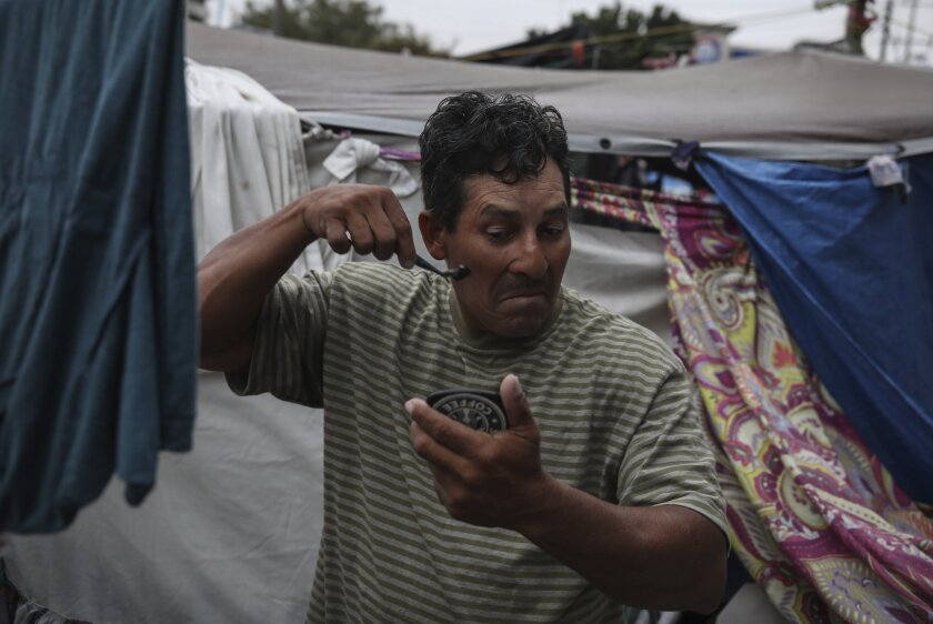 Honduran migrant Christian Fragoso holds a hand mirror in one hand as he shaves his face at a migrant camp near El Chaparral pedestrian border bridge in Tijuana, Mexico, Friday, July 2, 2021. The migrant camp of about 2,000 asylum-seekers, mostly families, blocks a pedestrian entrance to the US border crossing with San Diego. Mexican officials have suggested they will try to relocate them in coming days in anticipation that the two governments could agree to reopen the border to non-essential travel in the coming weeks. (AP Photo/Emilio Espejel)