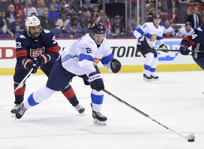 Finland defenseman Jyrki Jokipakka (2) reaches for the puck next to U.S. defenseman Dustin Byfuglien (33) during the first period of an exhibition game, part of the World Cup of Hockey, Tuesday, Sept. 13, 2016, in Washington. (AP Photo/Nick Wass)