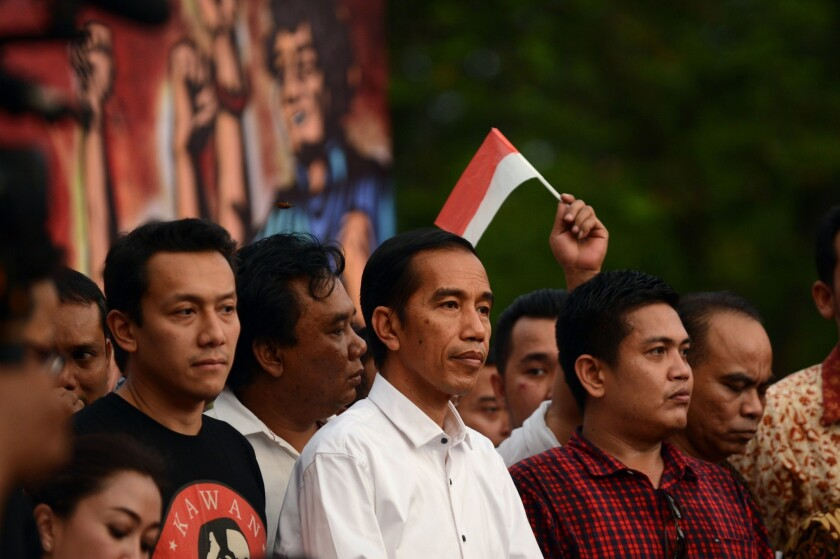 """After a tense two-week ballot recount in Indonesia's closest ever race for the top job, election officials declared the popular governor of Jakarta, Joko """"Jokowi"""" Widodo, center, the winner in the July 9 presidential election."""